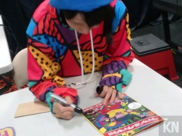 Chiaki autographing her English translated artbook for fans